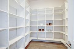 Pantry interior with empty shelves in a new home. White pantry interior with empty  wraparound shelves and dark wood floor. Northwest, USA Stock Photos