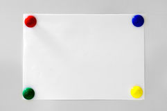 White paper. Hanging on grey background with four magnets colored blue, red, green and yellow Stock Photos