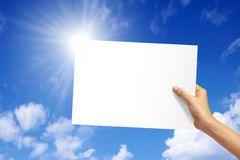 White paper. In woman hand on blue sky background stock photos