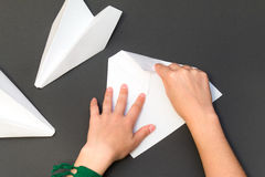 White paper airplane with clouds on a gray background. Person folding paper plane on a gray background Royalty Free Stock Photography