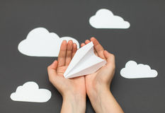 White paper airplane with clouds on a gray background. Person folding paper plane on a gray background Stock Photos