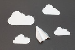 White paper airplane with clouds on a gray background. Person folding paper plane on a gray background Royalty Free Stock Images