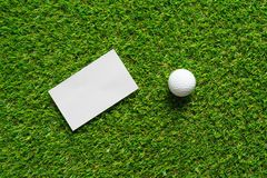 White paper background and golf ball on green grass of golf course. royalty free stock image