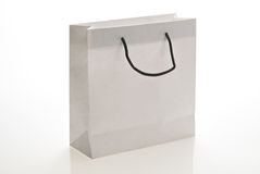 White paper bag with handle. Isolated on a white background. Clipping path included Stock Image
