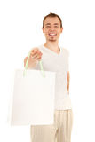 White paper bag from handsome man. Smiling handsome man is presenting white gift paper bag, isolated on white background. Focus on man's eyes royalty free stock photos