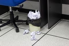 White paper balls into trash in work office stock images
