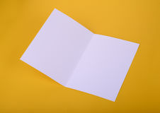 White paper bifold brochure mockup on yellow background Royalty Free Stock Photos