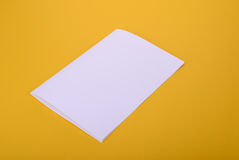 White paper bifold brochure mockup on yellow background Stock Images