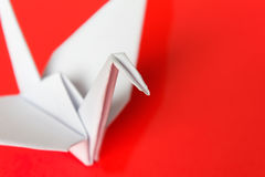 White paper bird. A white paper bird on a red background, shallow depth of field royalty free stock photo