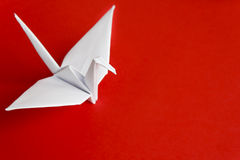 White paper bird. A white paper bird on a red background Royalty Free Stock Photos