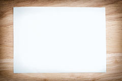 White paper blank on the brown wooden floor of vintage color. Royalty Free Stock Image