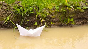 White paper boat. Floating in a puddle stock footage