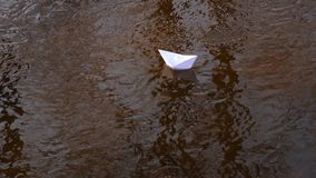 Small white paper boat is flowing along the river. White paper boat flows along river stock video footage