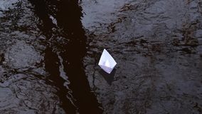 White paper boat that is reflected in the water carries current forwards. White paper boat that is reflected in water carries current forwards stock footage