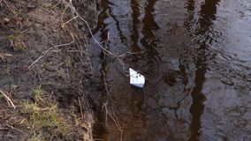 White paper boat sails along the river bank and it is pushed with a stick. White paper boat sails along river bank and it is pushed with stick stock footage