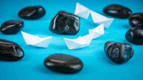 White paper boats in sigle file between abstract rock stones on blue background Royalty Free Stock Image