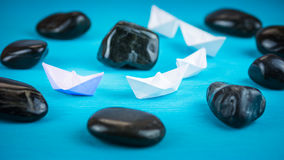 White paper boats in sigle file between abstract rock stones on blue background Royalty Free Stock Photography