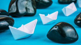 White paper boats in sigle file between abstract rock stones on blue background. Side Shot Stock Photo