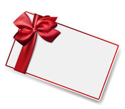 White paper card with gift red satin bow. Stock Photography