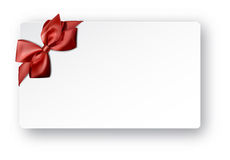 White paper card with gift red satin bow. Stock Image