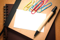 White paper card with pen. White paper card on notebook with pen on kraft cardboard background Stock Photography