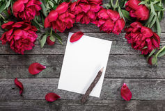 White paper card with pencil on rustic wooden background with pink peonies and petals. Flowers. Workspace Royalty Free Stock Images