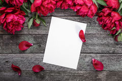 White paper card on rustic wooden background with pink peonies and petals. Flowers. Workspace. Royalty Free Stock Image