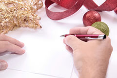 White paper for christmas greetings. White empty paper card with pen in hand and christmas ornaments in background Stock Images