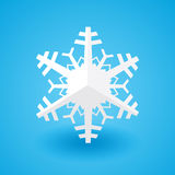 White paper christmas snowflake on a blue background with shadow. White paper cut of christmas snowflake on a blue background with shadow Stock Photo