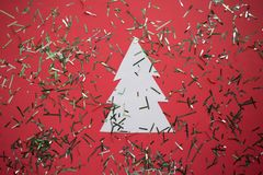 White paper Christmas tree, Festive confetti, christmas decoration on the red background with copy space royalty free stock images