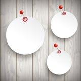 3 White Paper Circle Stickers Pin Wood. 3 white paper circle stickers with red pins on the wooden background Royalty Free Stock Image