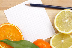 White paper with citrus border and blue pencil Royalty Free Stock Photos