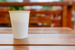 White paper coffee cup on wooden table outdoors. Stock Photo