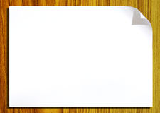 White paper with corner curl on wood Stock Photography