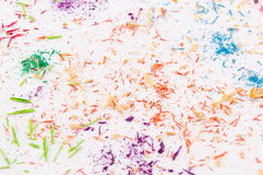 White paper covered in colored pencils sharpening leftovers Royalty Free Stock Image