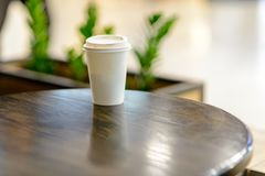 The white paper cup with coffee against the background of the blurry lights. A white paper cup with coffee from  against the background of the blurry lights of stock photos