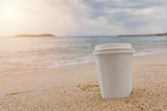 White paper cup of coffee on the sea water and beach sandy background stock photos