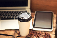 White paper cup of coffee on wooden desk and laptop. White paper cup of coffee on wooden desk Royalty Free Stock Photo