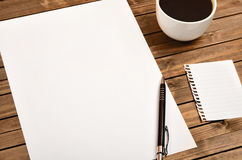 White paper with cup of coffee. On wooden table Stock Photography