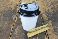 White paper cup of coffee. On a wooden table Royalty Free Stock Photos