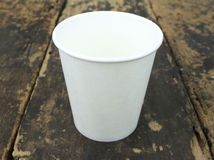 White paper cup of coffee. On a wooden table Stock Photography