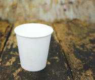 White paper cup of coffee. On a wooden table Stock Image