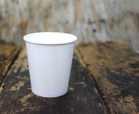 White paper cup of coffee. On a wooden table Stock Images