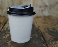 White paper cup of coffee. On a wooden table Royalty Free Stock Images