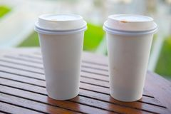 White paper cup for hot coffee or hot tea. Two white paper cup for hot coffee or tea on wood table Royalty Free Stock Photos