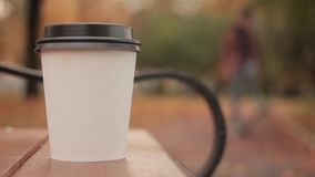 White paper cup with hot drink in autumn city park close up with defocused background skater boy walking people. White paper cup with hot drink in autumn city stock video footage