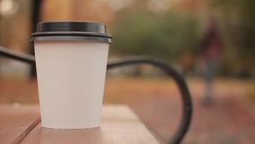 White paper cup with hot drink in autumn city park close up with shot defocused background skater boy picks up the paper. Cup HD stock footage