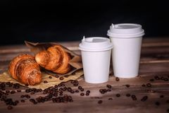 White paper cups with caps presented in front . Coffee cup and coffee beans , croissant , on brown wooden table Stock Images