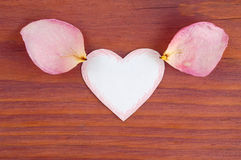 White paper cut heart with red hatch on edges and rose petals on each side lying on wooden table Stock Photo