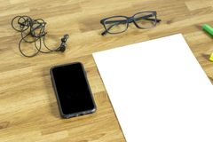 White paper with earphone,cellphone,glasses and high lighter Stock Photos